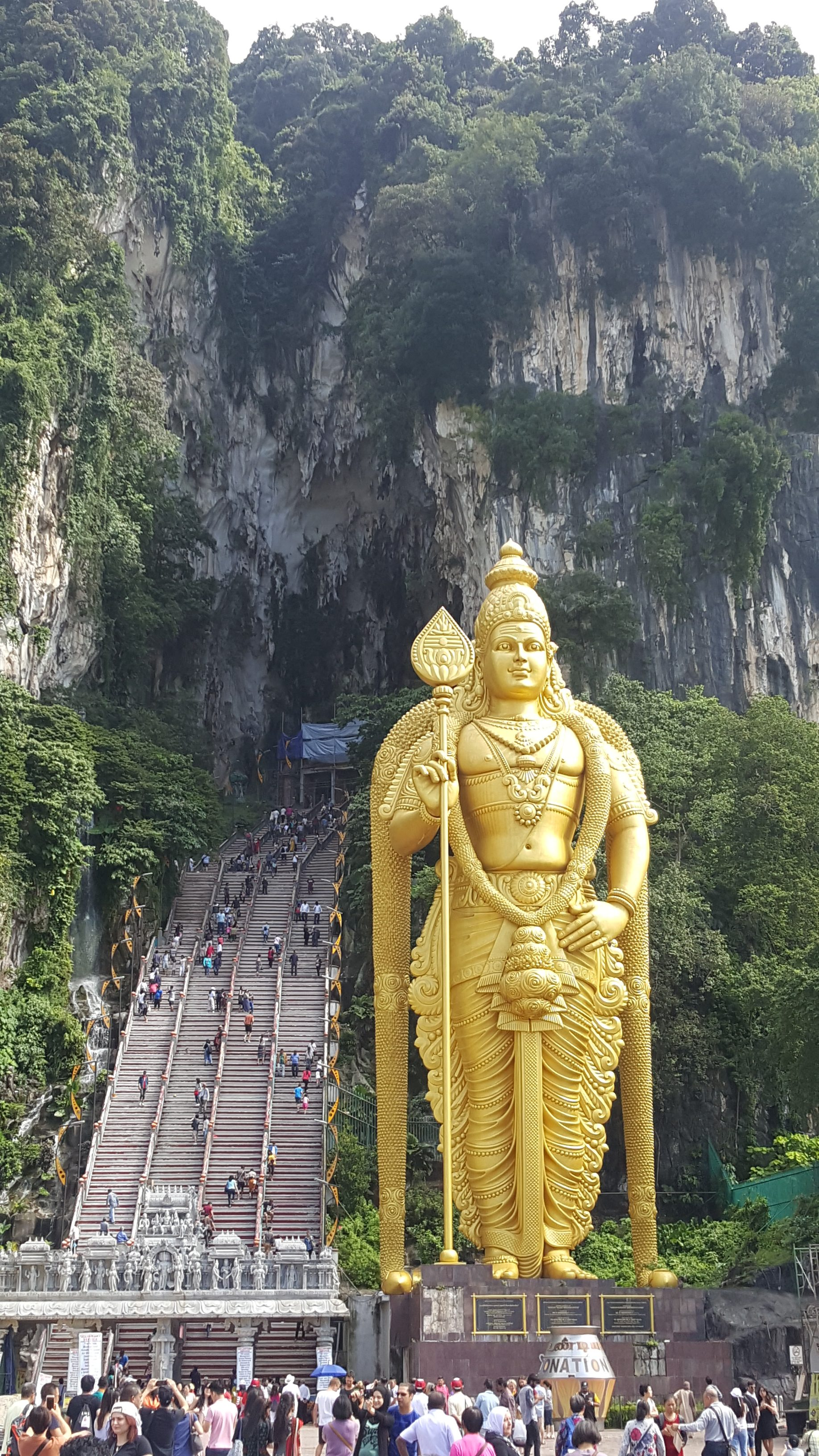 The entrance to the Batu Caves, set into a large hillside with 272 steps leading up, and a 140 foot gold hindu statue marking the entrance to the steps. Crowds walk up and down the steps and congregate at the bottom