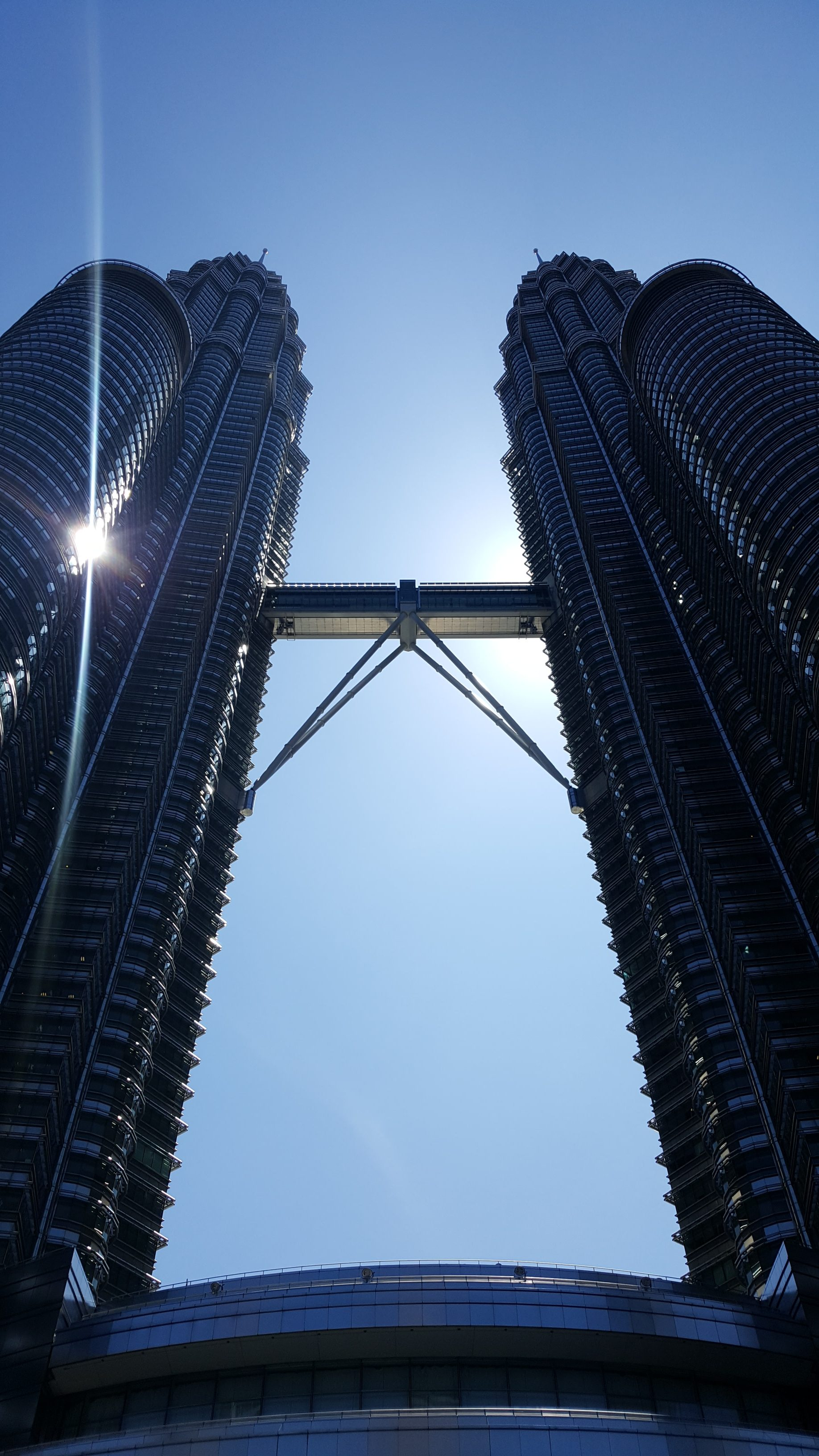 The Petronas towers, taken near midday with the sun reflecting off the glass. The photo is taken from the ground floor, looking up