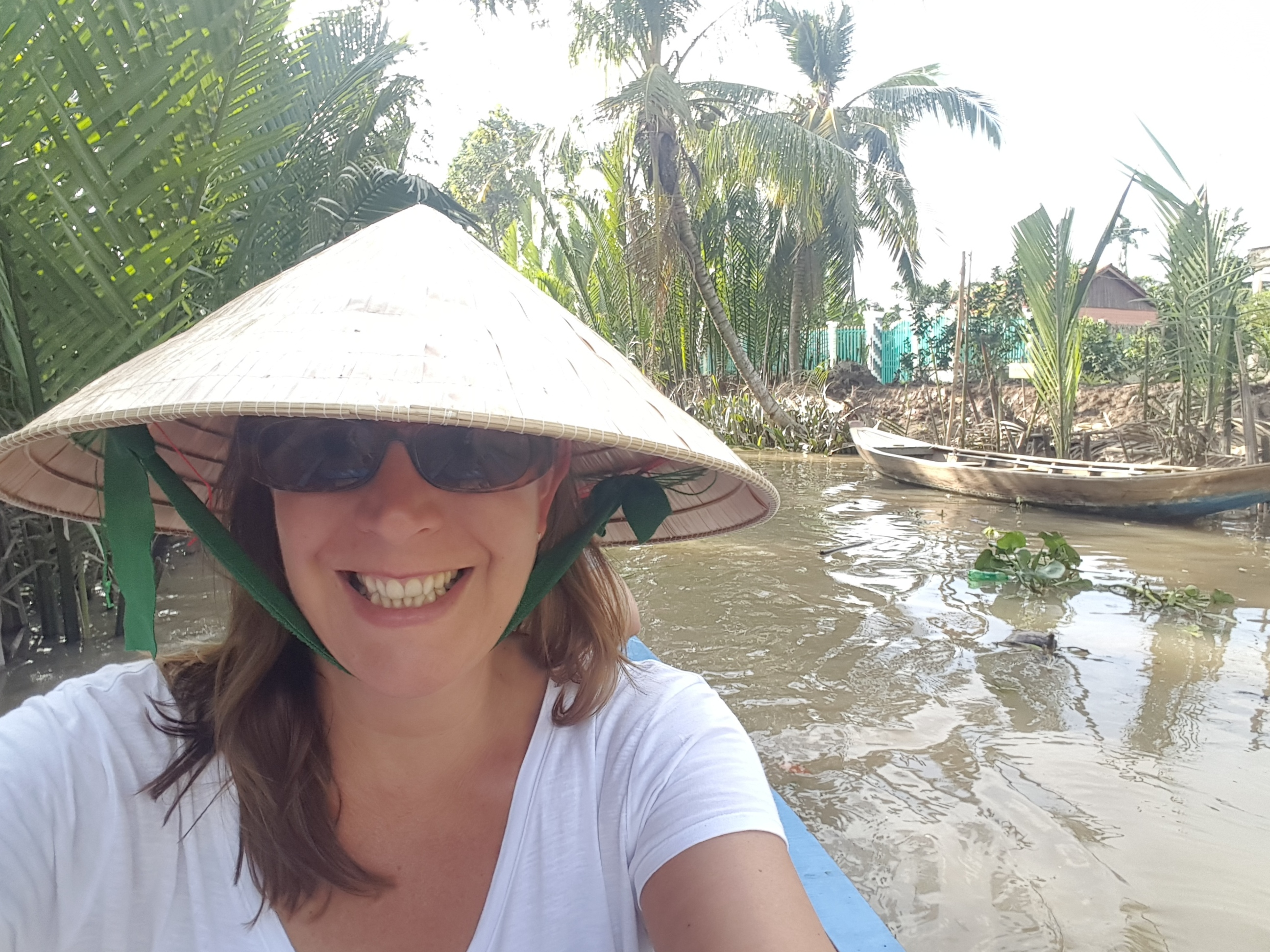Me wearing a Vietnamese straw hat, smiling broadly, I am in a small wooden boat, rowing along a muddy canal lined with tropical trees