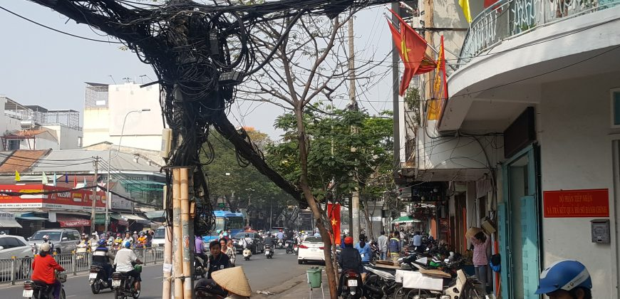 An electricity pole on a busy street is packed with a mangle of black electric wire