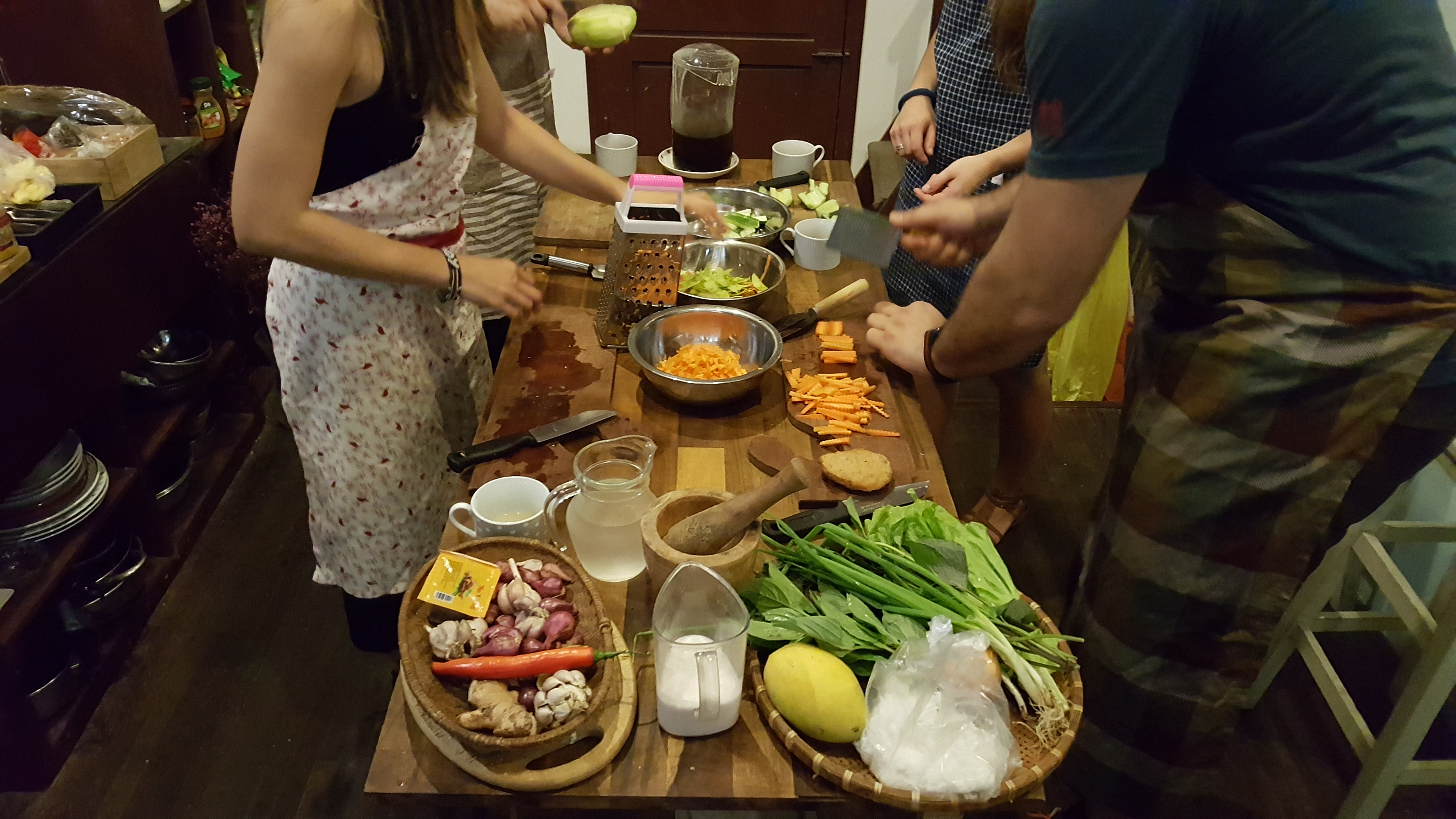 A table full of dishes of vegetables with people chopping and mixing food