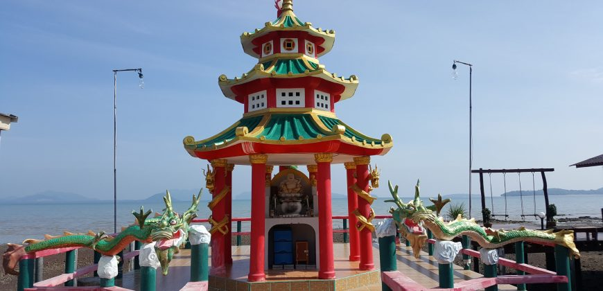 A monument of red pillars and curvy green roofs, surrounded by a railing made of green wooden dragons. In the background is the sea and distant islands