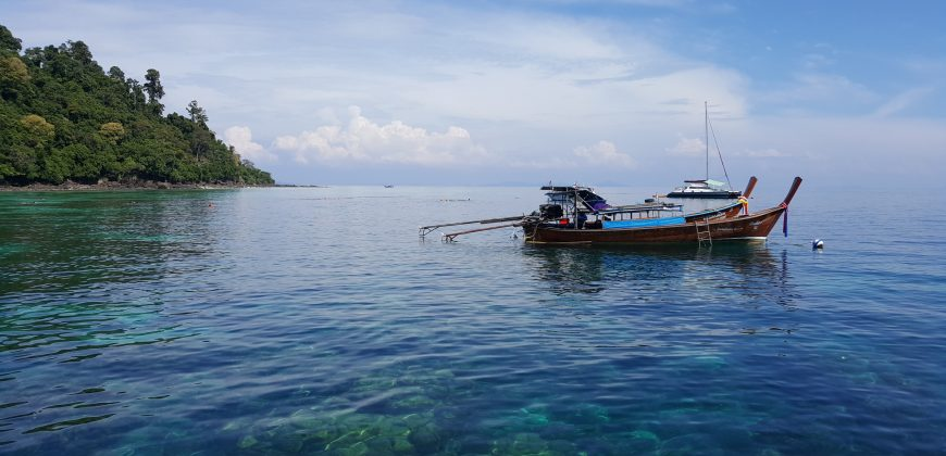 A wooden boat floating on clear water with the reef visible below and a rocky island outcrop in the background