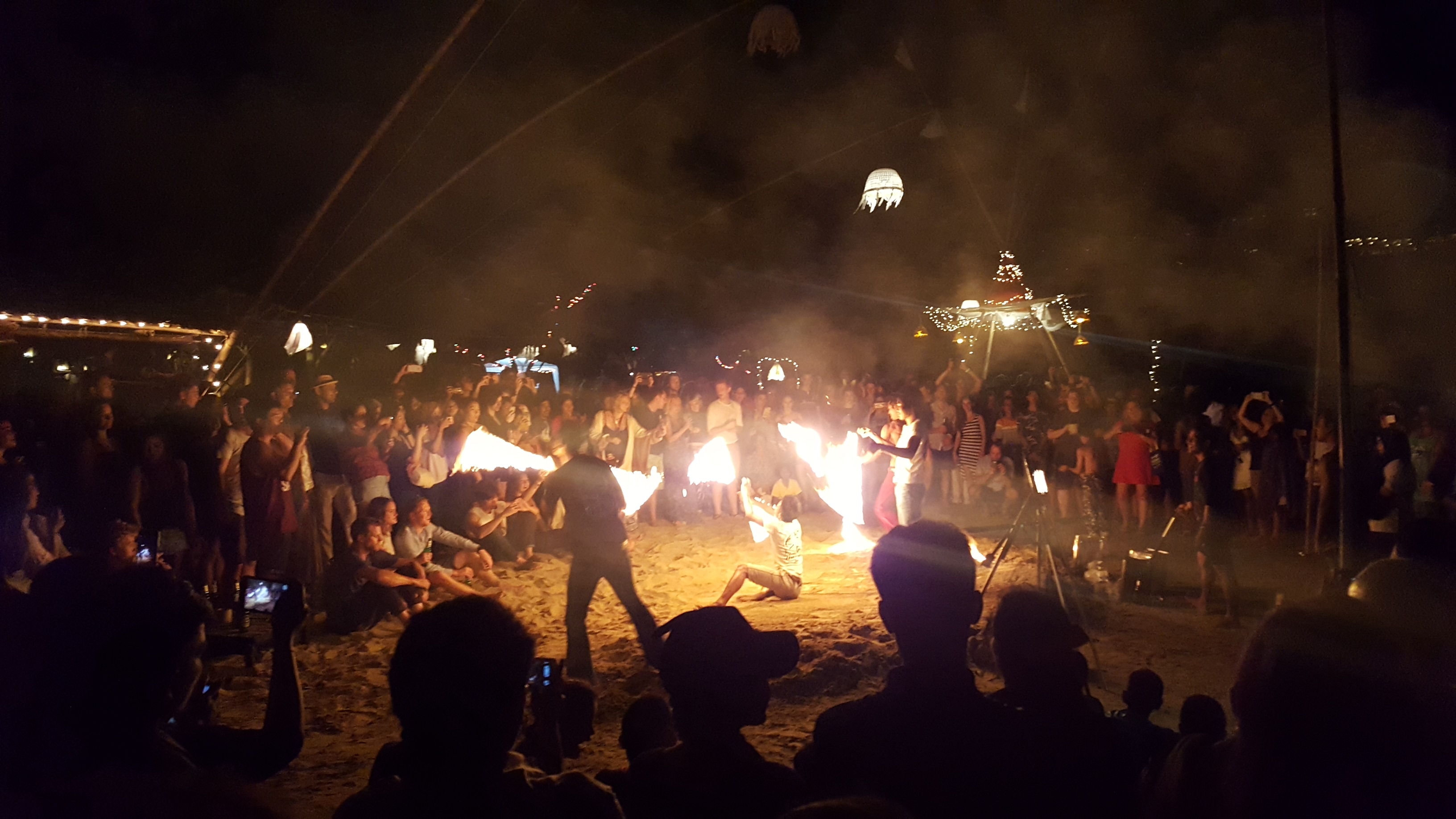 Three men juggle fiery batons on the beach after dark, surrounded by crowds