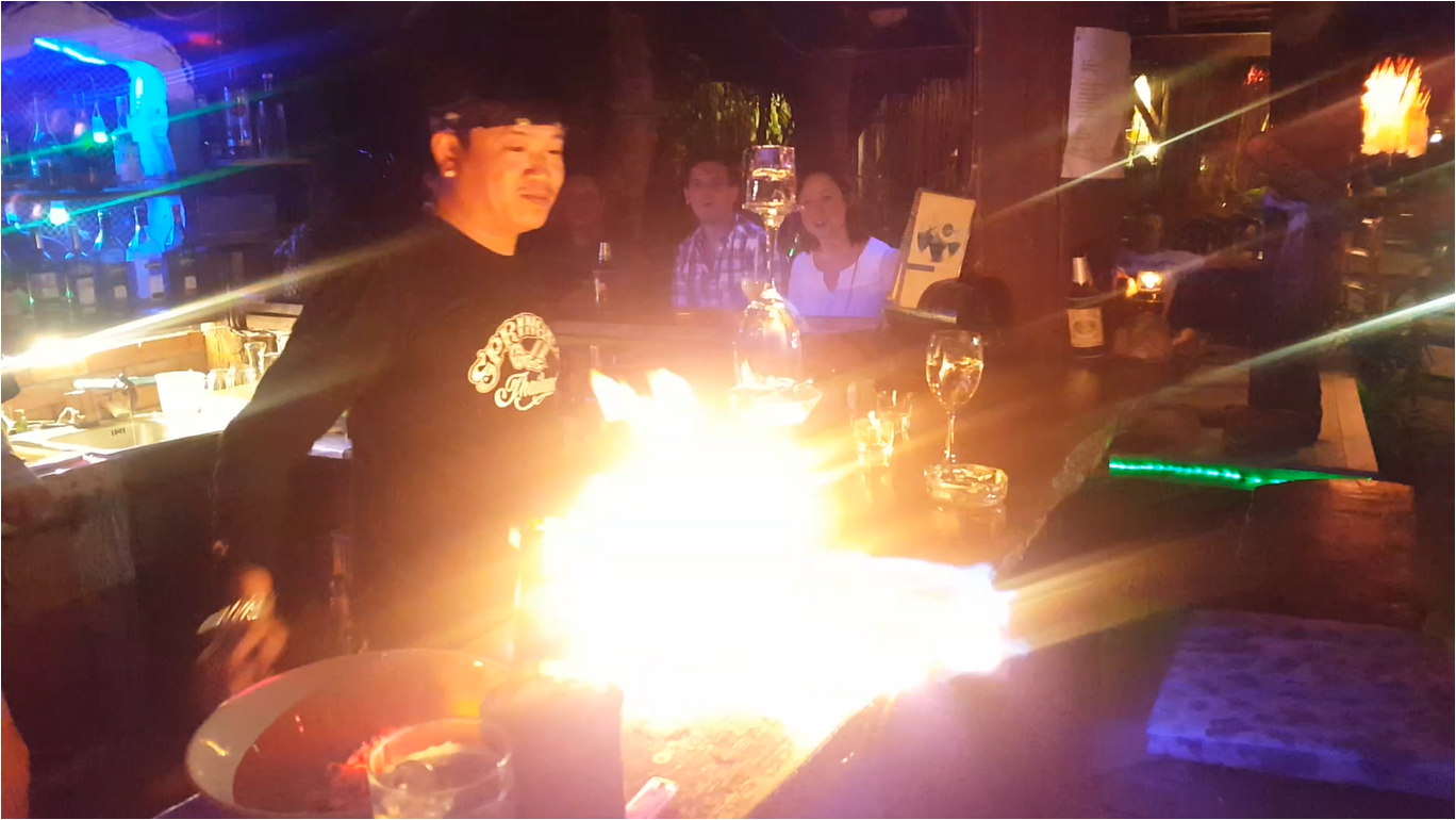 A bartender lights alcohol cascading from a pyramid of glasses on the bar