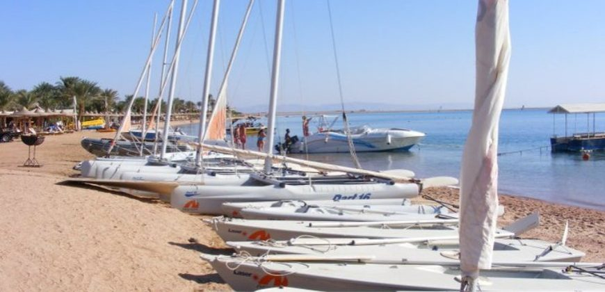 A row of dinghy boats along the beach by the sea