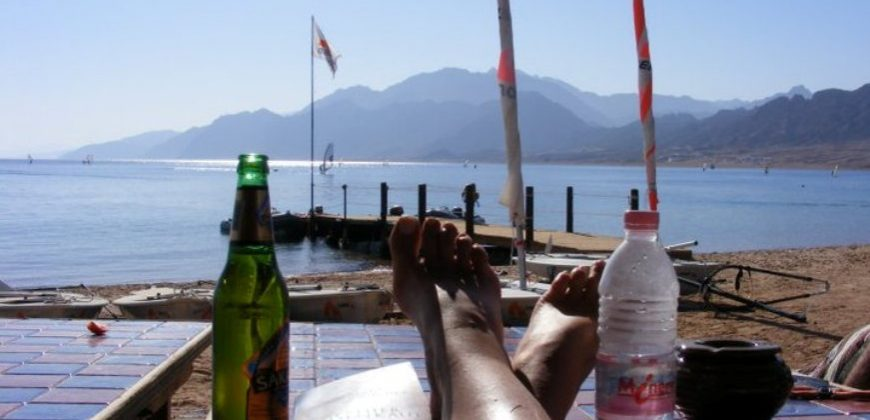 My feet propped up on a low table with my book, a beer and a bottle of water overlooking the sea