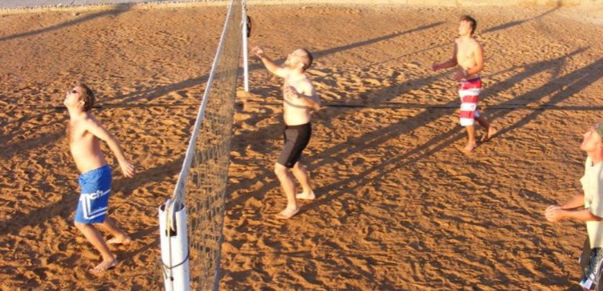 Young men playing volleyball on the beach in the late afternoon sun