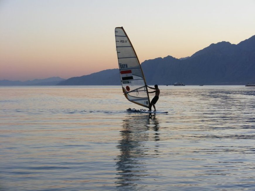 A windsurfer at sunset, on a calm sea with a purple and grey mountain range behind him