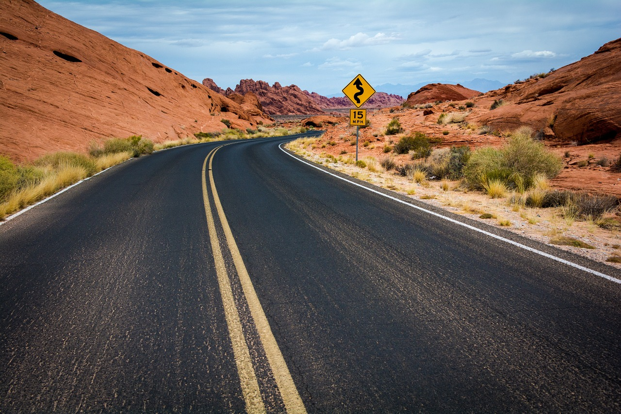 An Australian black tarmac road bordered by red rocky hills with a winding road sign