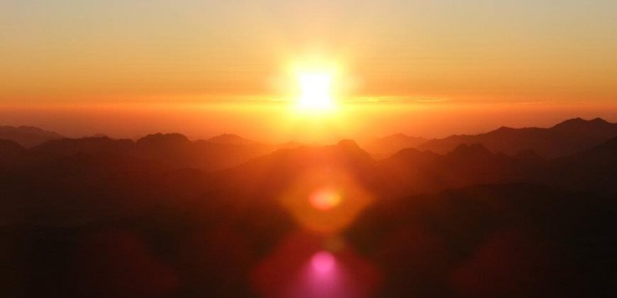 The rising sun over the mountains, filling the sky with oranges and pinks