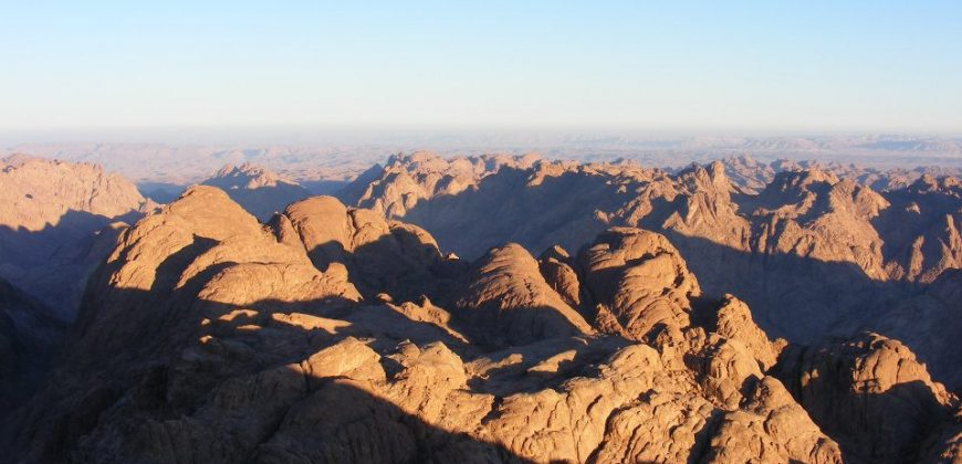 Mount Sinai sunrise with skies of blue and a rocky mountain range of brown, purple and grey