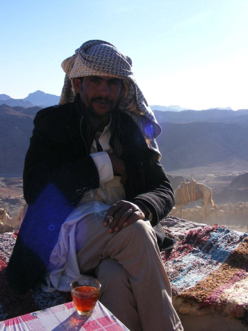 Our guide sat on mats at an outdoor cafe on the mountain with a glass of tea in front of him. A camel and mountains are in the background, hazy in the morning sun. Our guide is wearing a traditional head scarf, long coat and robes. He is smoking and stares intently at the camera.