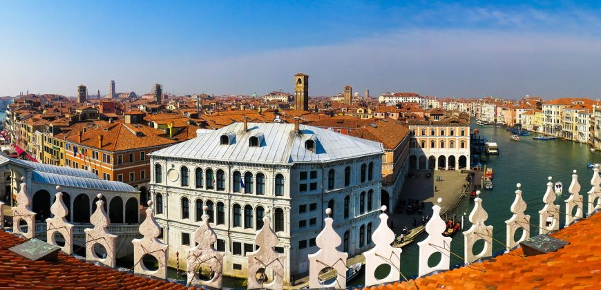 A panoramic view of Venice, showing canals, a terracotta tiled rooftop and old buildings lining the canals
