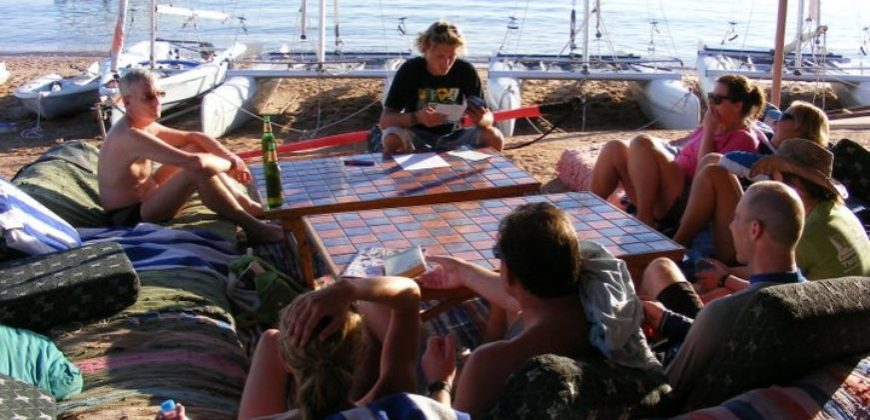 A group of people sat on patterned cushions and mats around a low tiled table, learning windsurfing theory. The sea and small dinghy boats are in the background