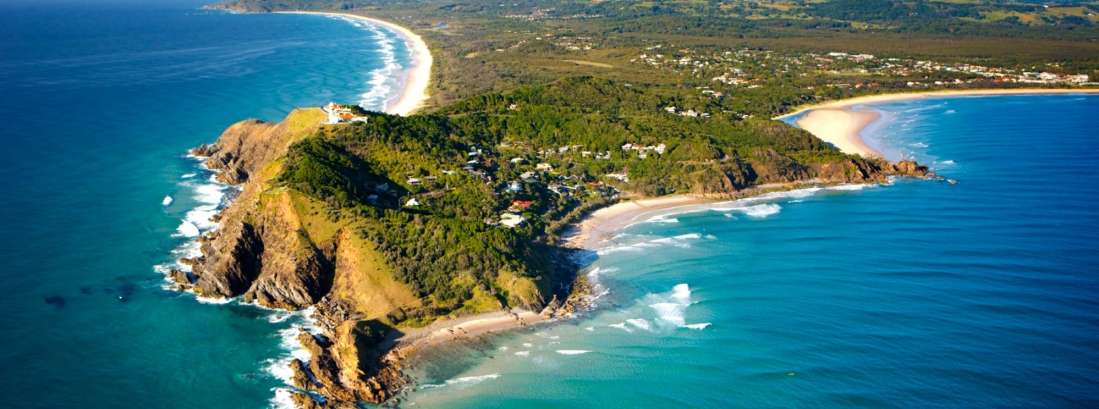 Craggy coastline with some sandy beaches and lush green hills, surrounded by lovely blue seas