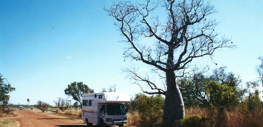Our motorhome parked by a boabab tree on an orange dirt road