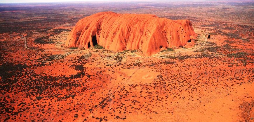 Uluru from the air. The large orange rock is surrounded by orange earth dotted with green shrub