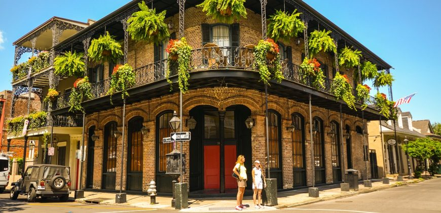 A classic New Orleans style house on a street corner with wrought iron wrap around balcony and hanging baskets of greenery