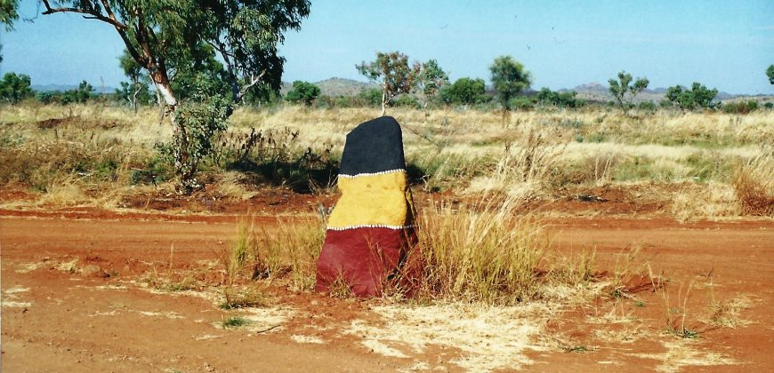 A rock at the side of an orange dirt road painted in 3 bands of black, yellow and red, in aboriginal style