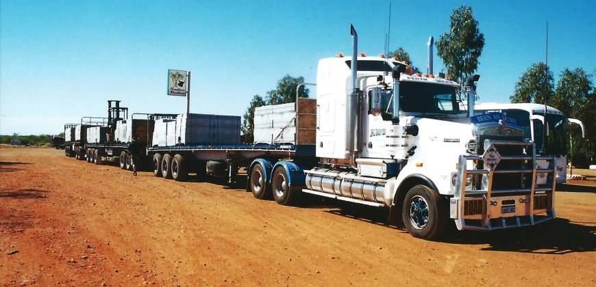 A road train - a truck with several trailers, parked on orange earth