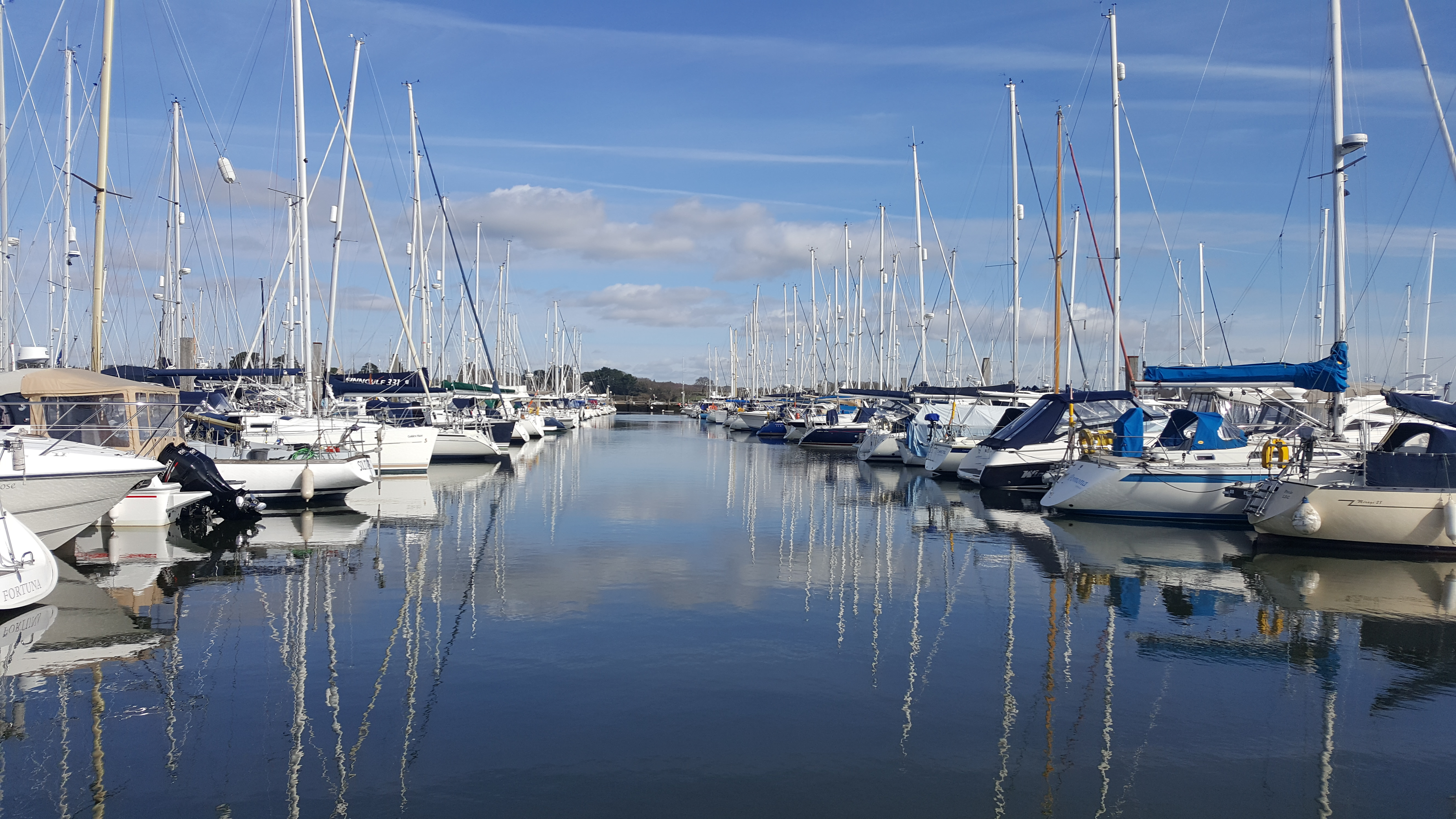 A marina with flat water and boats on a sunny day