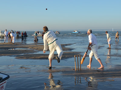 A game of cricket being played in the shallow sandbank early morning