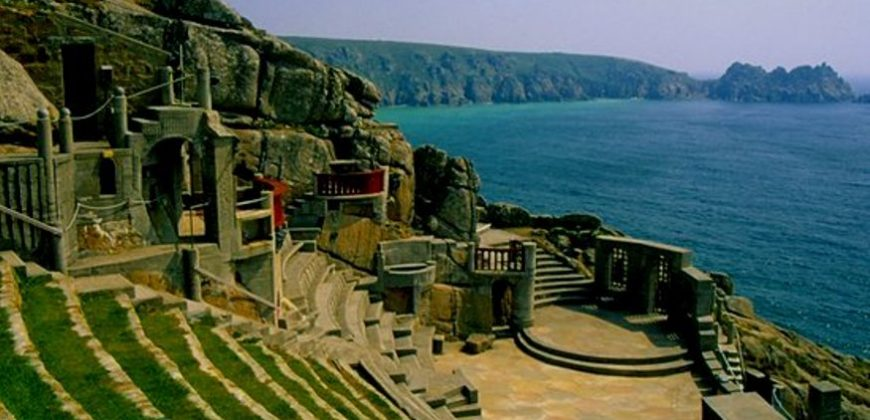 Minack Theatre with its grass and stone amphitheatre overlooking the stone stage, with the cliffs, blue sea and distant coastline in the background