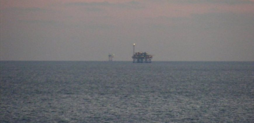 Oil rigs visible from the shore