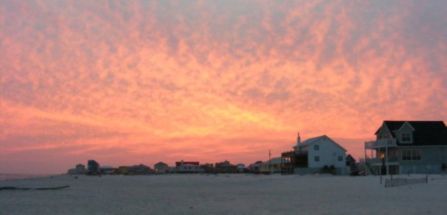 Pink and orange sunset skies over the sandy beach, with wooden beach houses nearby