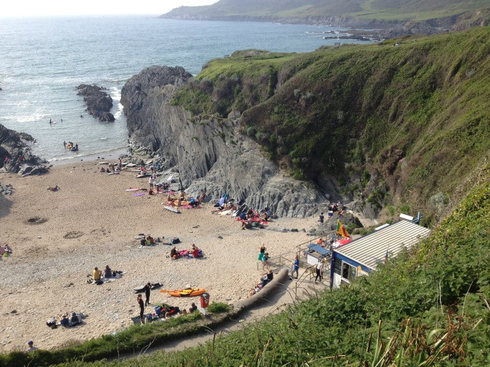 A sandy cove with a few people sunbathing on the beach and against the rocks, with the sea in the background