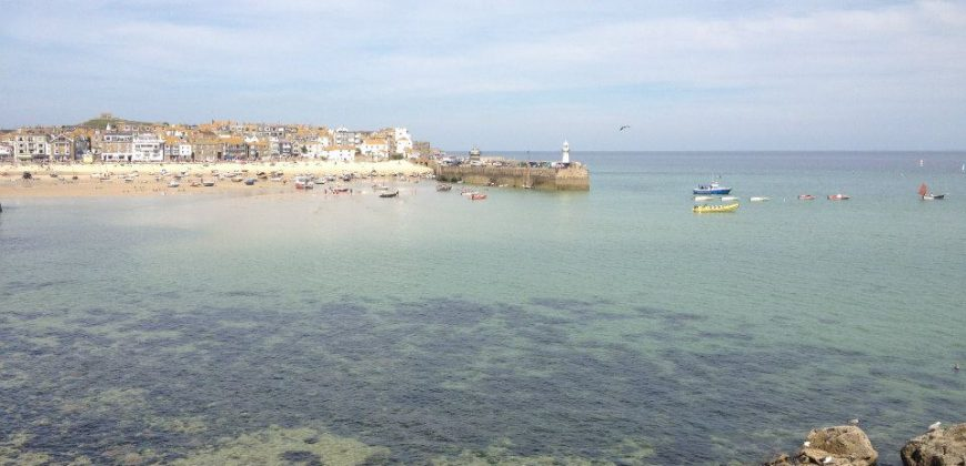 St Ives shoreline with clear waters, the harbour and town in the background