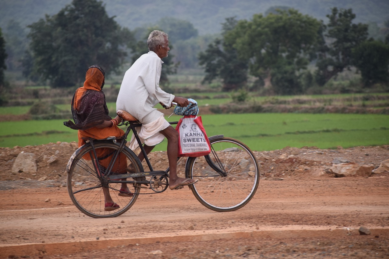 An elderly couple on a bike, the man is cycling, the lady is sat side saddle on the back. They are cycling along a dirty road with grassy fields and trees in the background