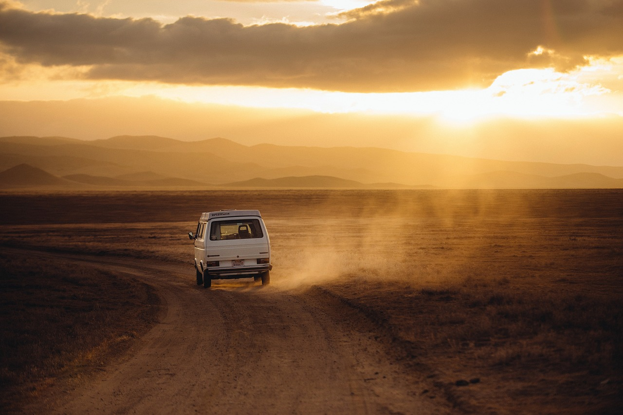 A VW campervan driving along a dusty dirt road at sunset