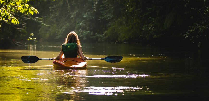A girl kayaking solo down a calm stream, surrounded by trees with dappled sunlight shining through