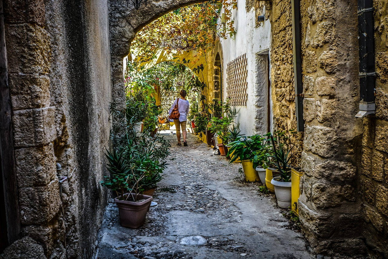 A lady walking down a small alleyway lined with old hosues and pot plants