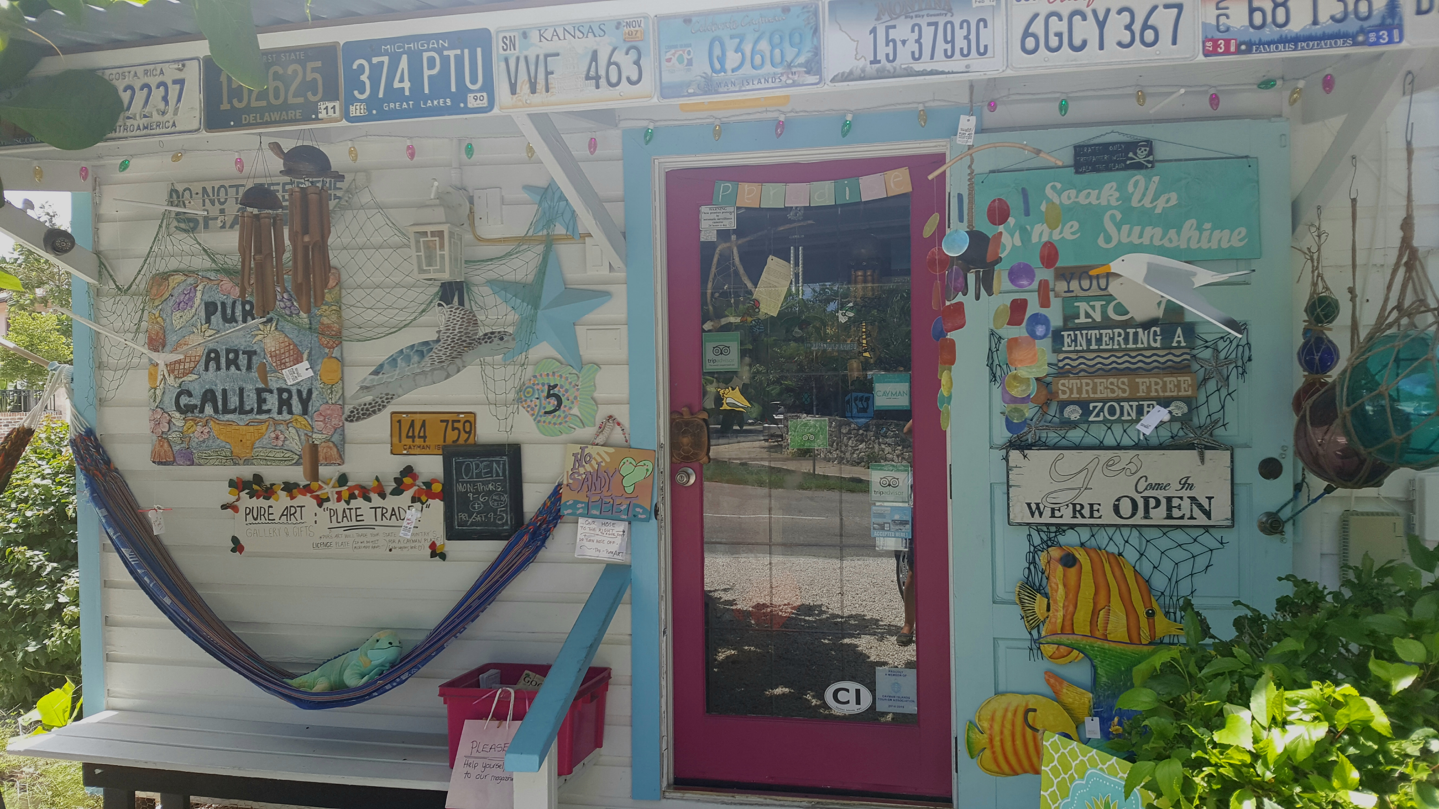 Pure Art gallery in South Sound, a rustic Caribbean wooden bungalow painted in white, blue and pink and decorated with chimes, paintings, American license places and shells.