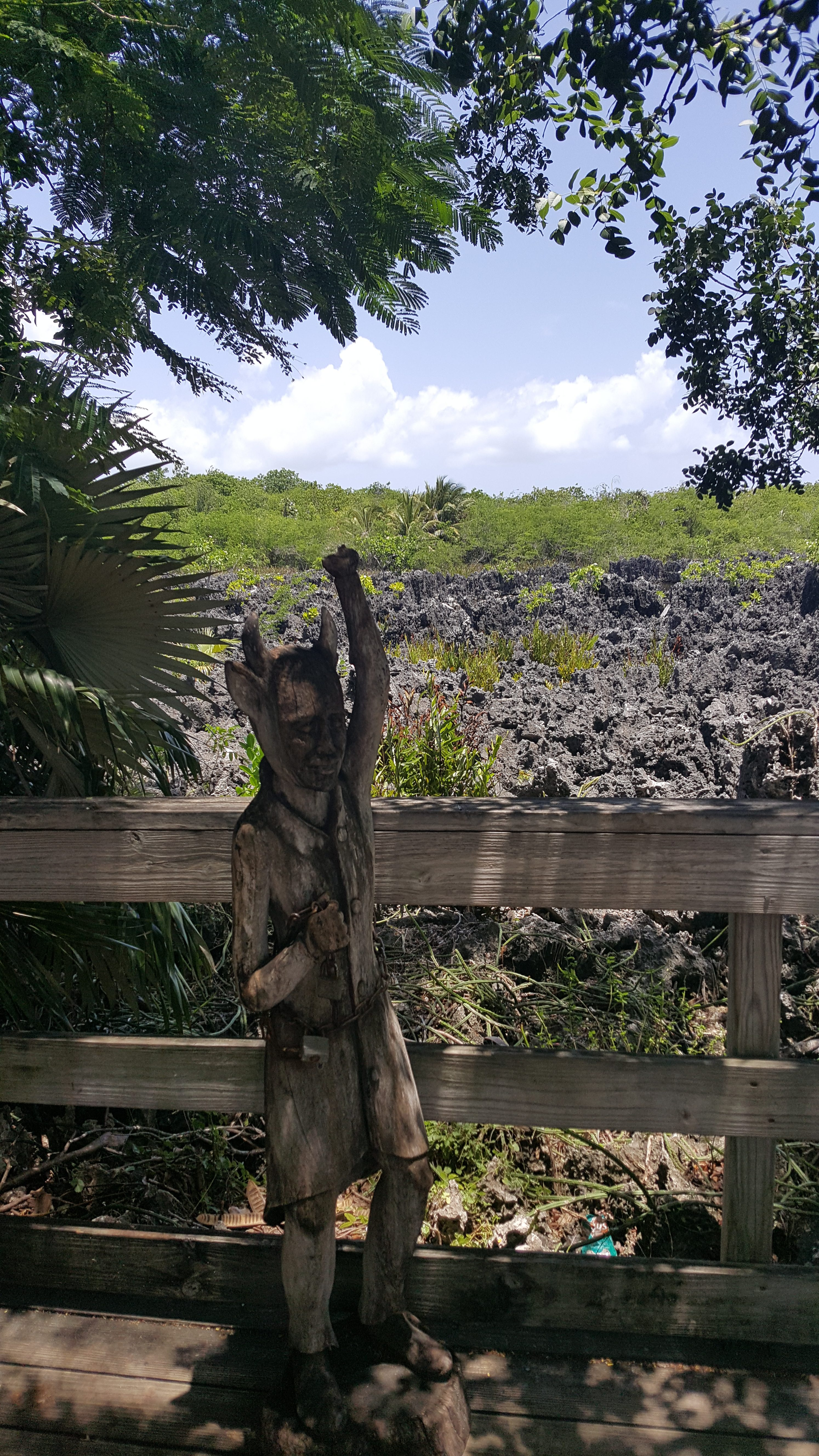 A wooden carving of the devil at a viewing area overlooking the black, gnarly rock dotted with palms and bristly greenery