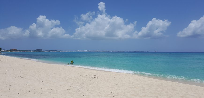 The white sands of Seven Mile Beach overlooking aqua water, with a gorgeous bright blue sky dotted with fluffy clouds hugging the shoreline