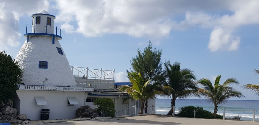 East End lighthouse, a tiny white lighthouse on the waterfront overlooking the Caribbean sea, bordered by palm trees