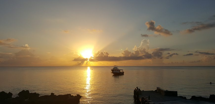 A sunset view from Sunset house - the sun is setting behind a cloud, throwing a line of burning orange over the sea. A boat is near the shore with a craggy coastline in the foreground