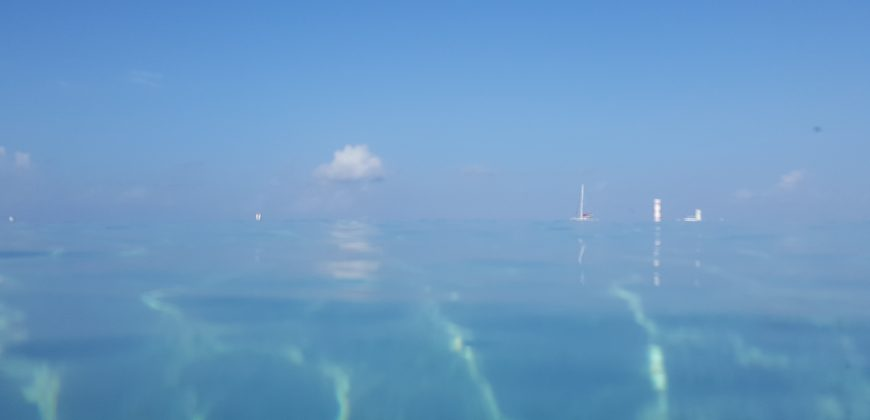 Where the sea meets the sky. Taken from the sea right on the surface, the colour of the sea and sky is identical, only the boats and clouds show where the horizon is