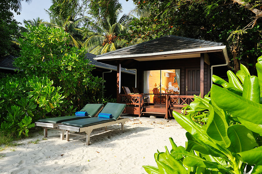 Beach bungalow from outside, with a sheltered balcony and sunloungers on the private beach area