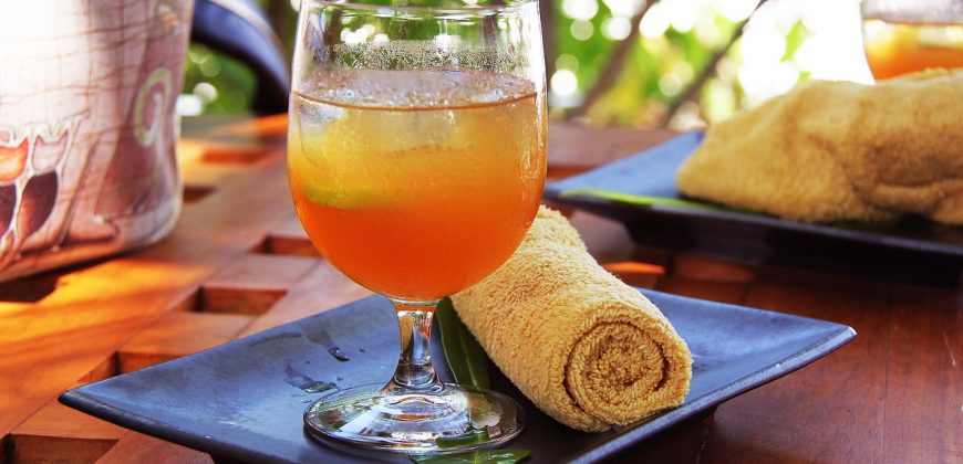 A welcome drink of fresh juice served on a plate with a cold towel