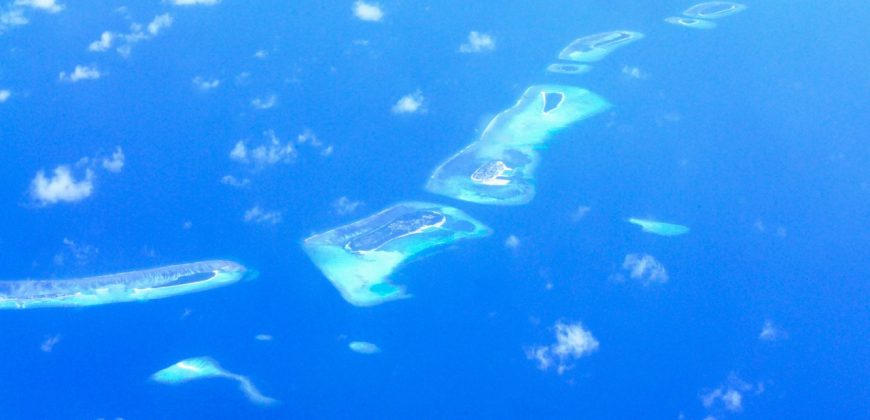 The Maldives from the air - a string of tiny islands surrounded by blue seas