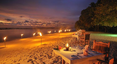 Sunset beach dinner, tables are set on the beach with linen tablecloths and candles, tiki torches line the water and the sky is pink, purple and blue. It's a romantic setting