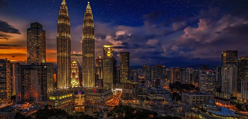 The Petronas towers at night, light up and surrounded by office buildings and a starry, partly cloudy blue and orange sky