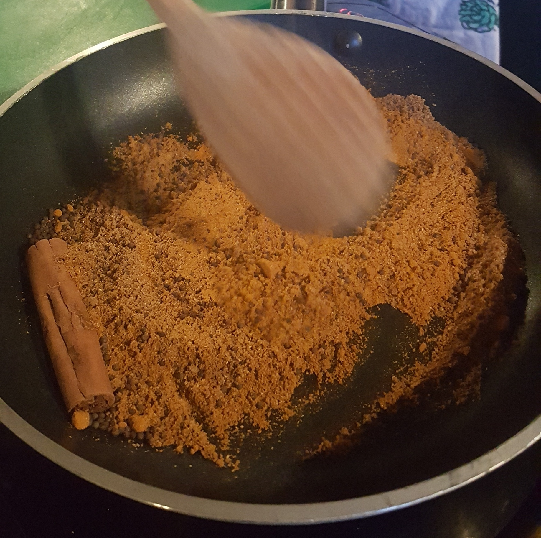A frying pan with spices and a cinnamon stick