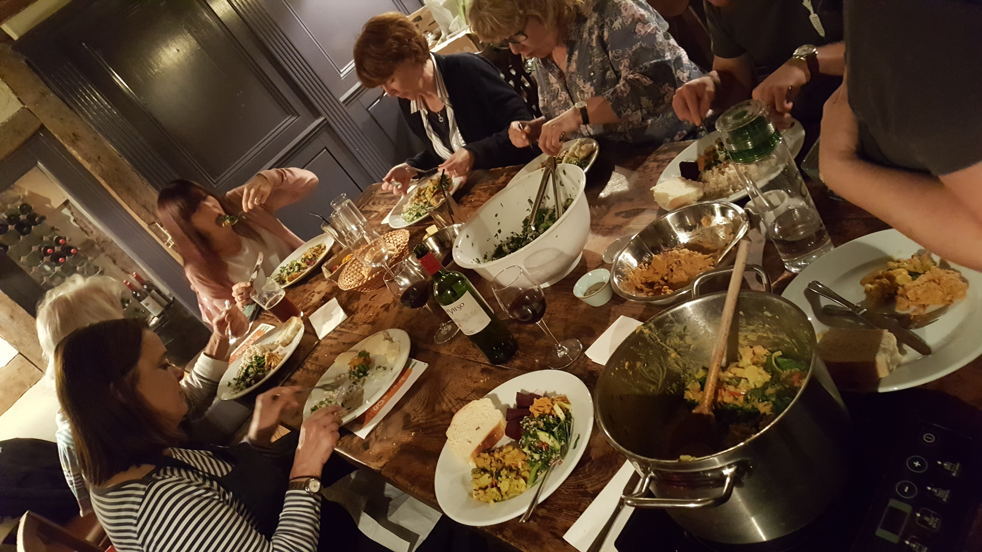 The feast: our group tucking into our dinner at a big wooden table with our dishes spread between the place settings