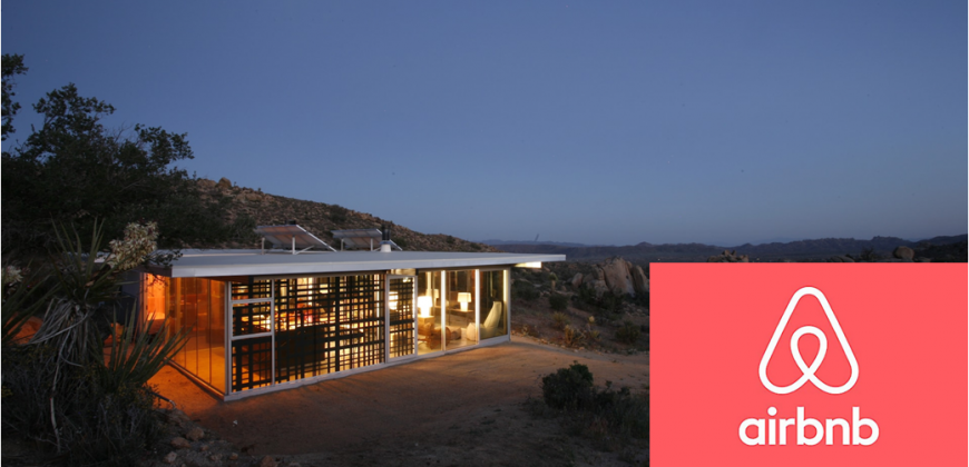 Desert house set under an early evening sky with stars. Airbnb logo appears on the photo as this is an Airbnb property